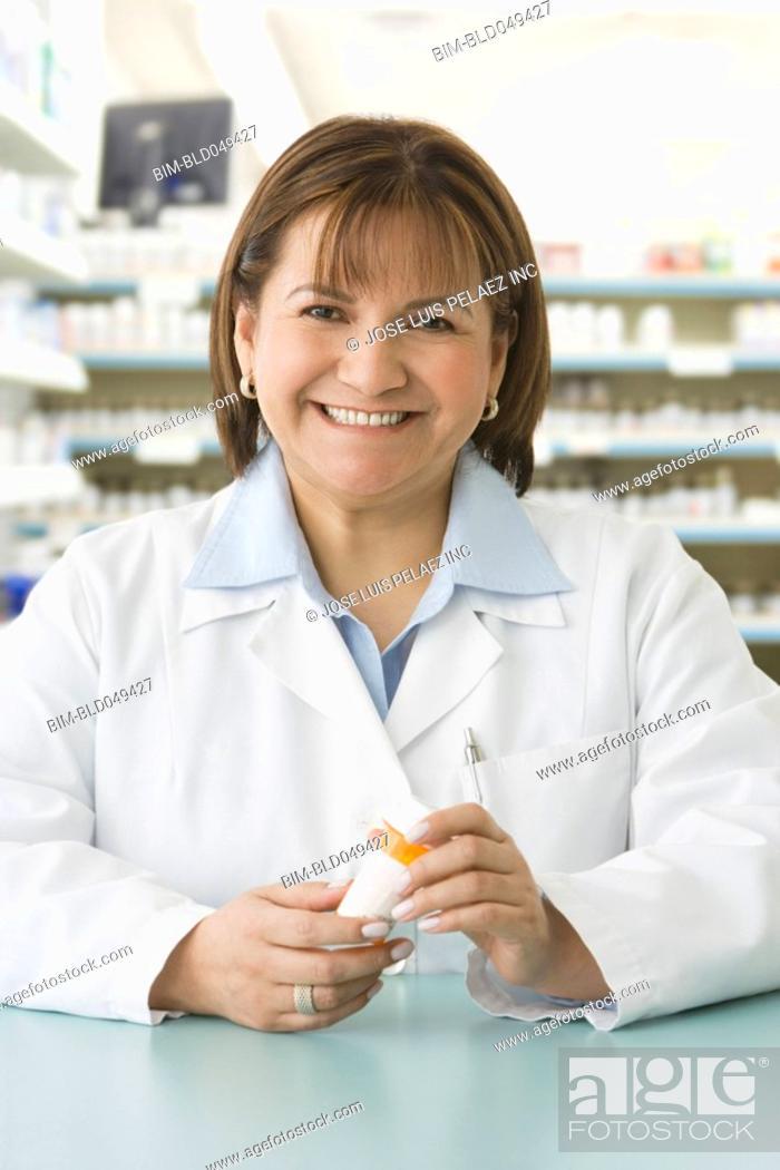 Stock Photo: Hispanic female pharmacist holding medication.