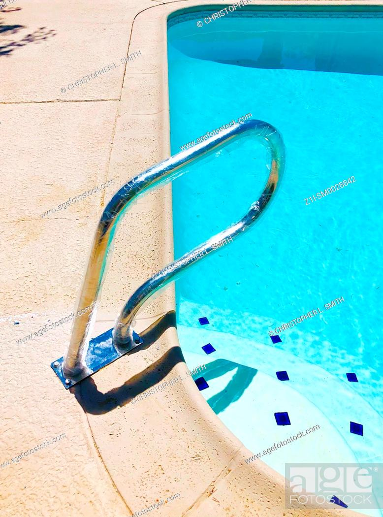 Stock Photo: Handrail affixed to the edge of a swimming pool near the steps into the shallow end.