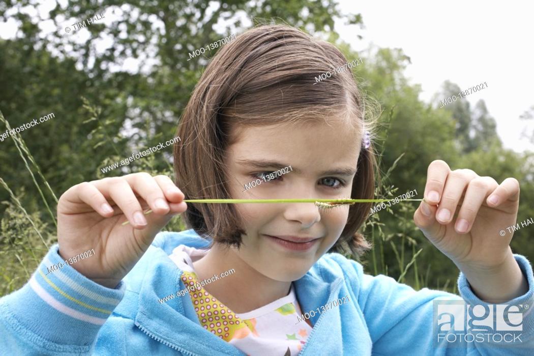 Stock Photo: Girl 7-9 examining caterpillar on grass in field.