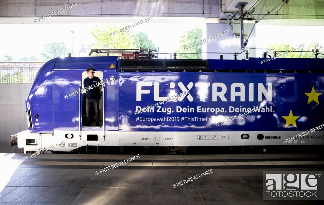 Stock Photo: 23 May 2019, North Rhine-Westphalia, Cologne: Jannick Dahm, locomotive driver, is standing in the door of the locomotive of a Flix Train in the station.