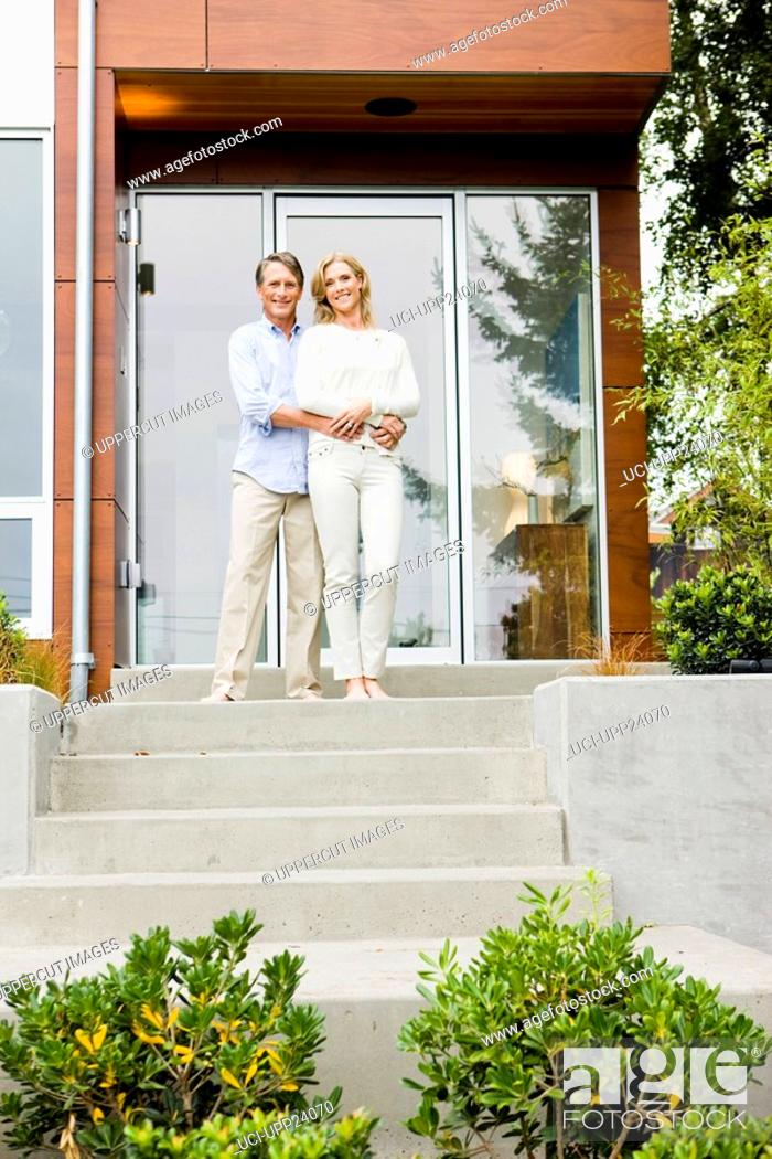 Stock Photo: Portrait of couple hugging on front stoop of modern house.