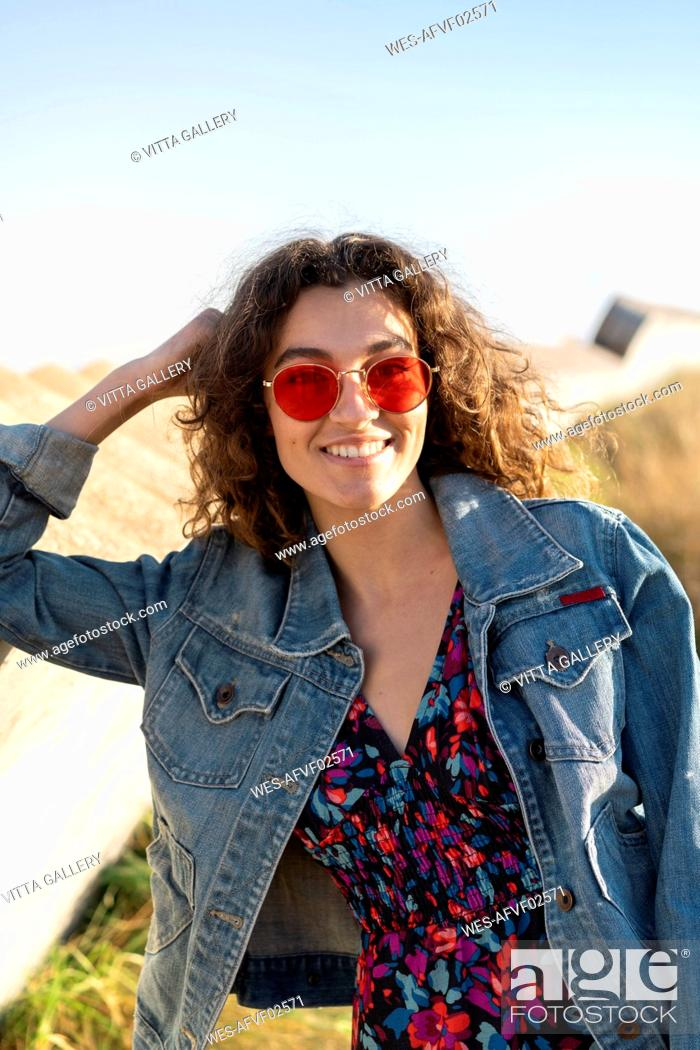 Stock Photo: Portrait of happy young woman with curly brown hair wearing red sunglasses leaning on a wall.