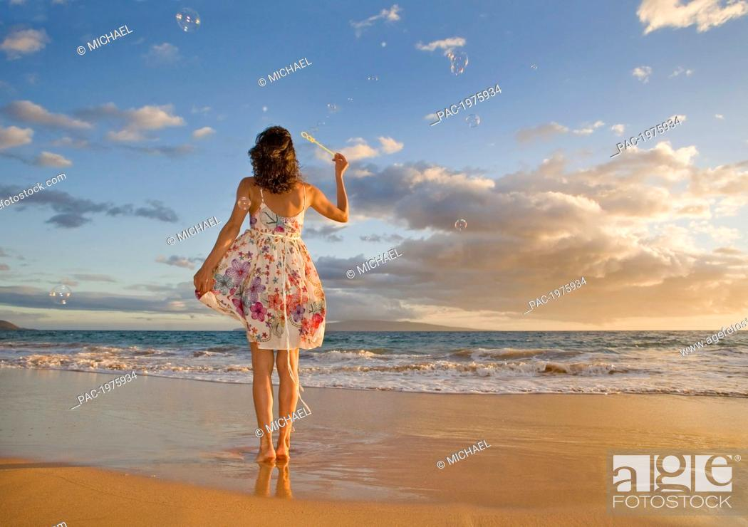 Imagen: Hawaii, Maui, Woman Standing On The Shore Of Remote Tropical Location Blowing Bubbles.