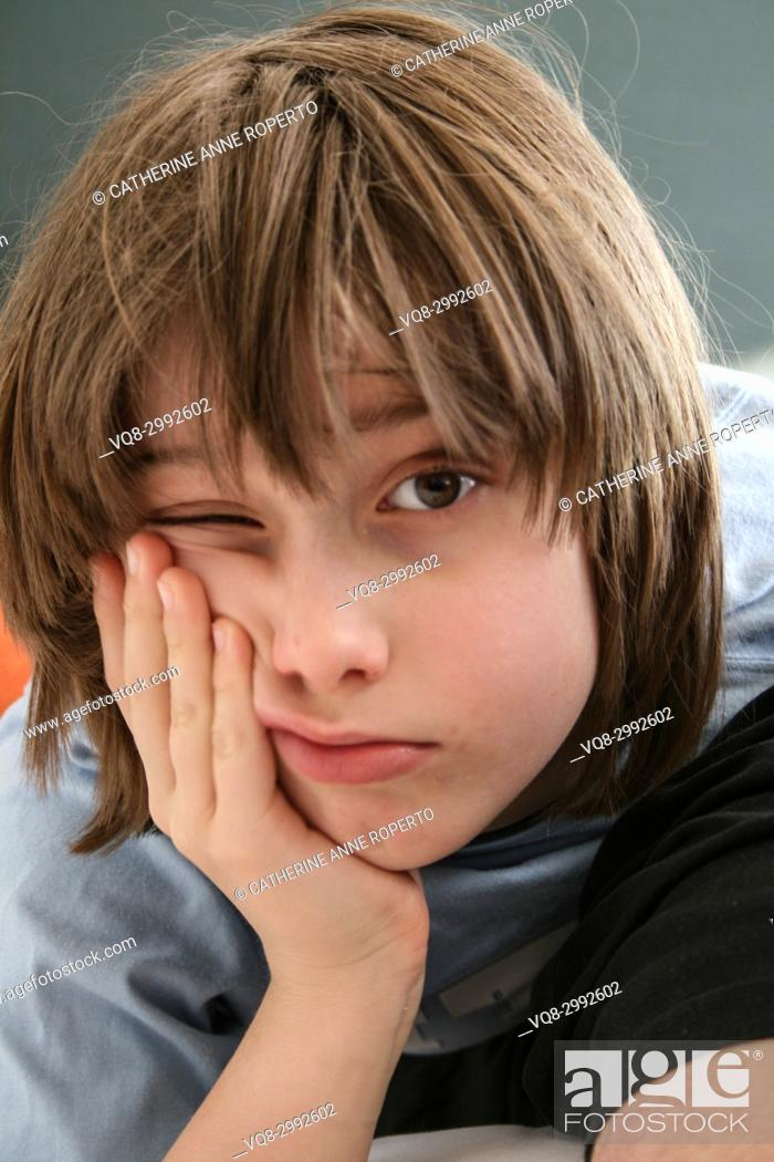 Stock Photo: Young boy with messy brown hair leaning his cheek on his hand with one eye open in Brussels, Belgium.