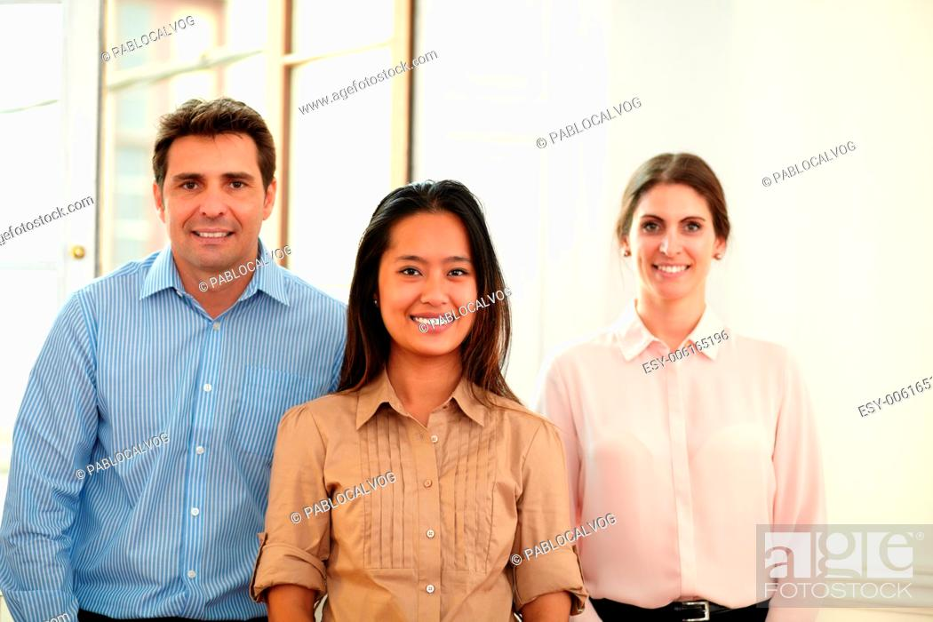 Stock Photo: Portrait of man and woman group smiling at you while standing on office background.