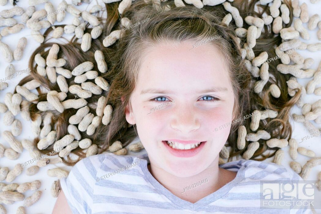 Stock Photo: young girl looking at camera surrounded by peanuts.