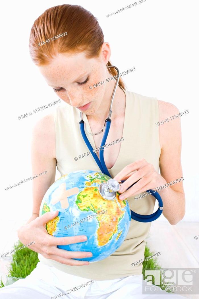 Stock Photo: young woman examinating globe.
