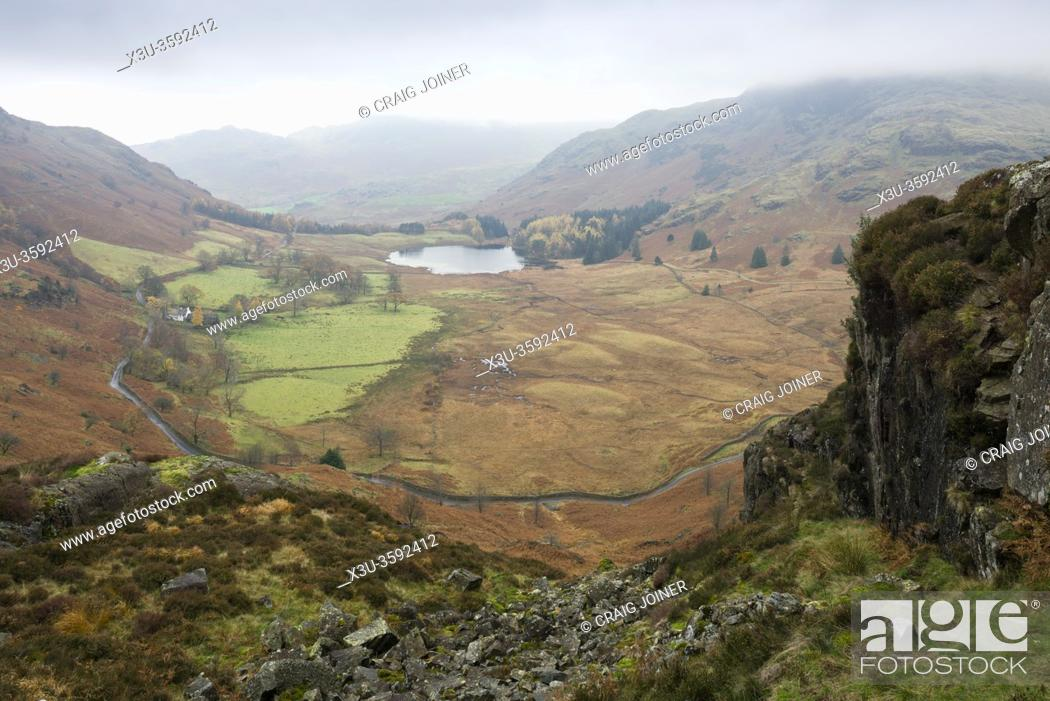 Stock Photo: Blea Tarn in the valley between Lingmoor Fell and Wrynose Fell from Side Pike with Wetherlam in the clouds beyond. Lake District National Park, Cumbria, England.