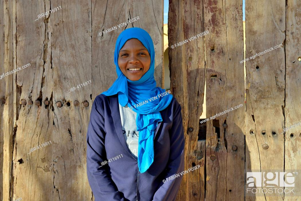 Stock Photo: Young woman with headdress, against a wooden door, portrait, Karima, Northern, Nubia, Sudan.