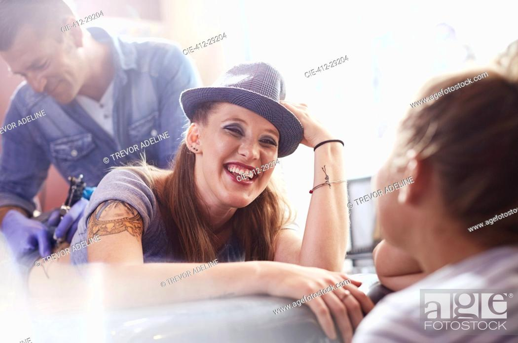 Stock Photo: Smiling woman getting a back tattoo.