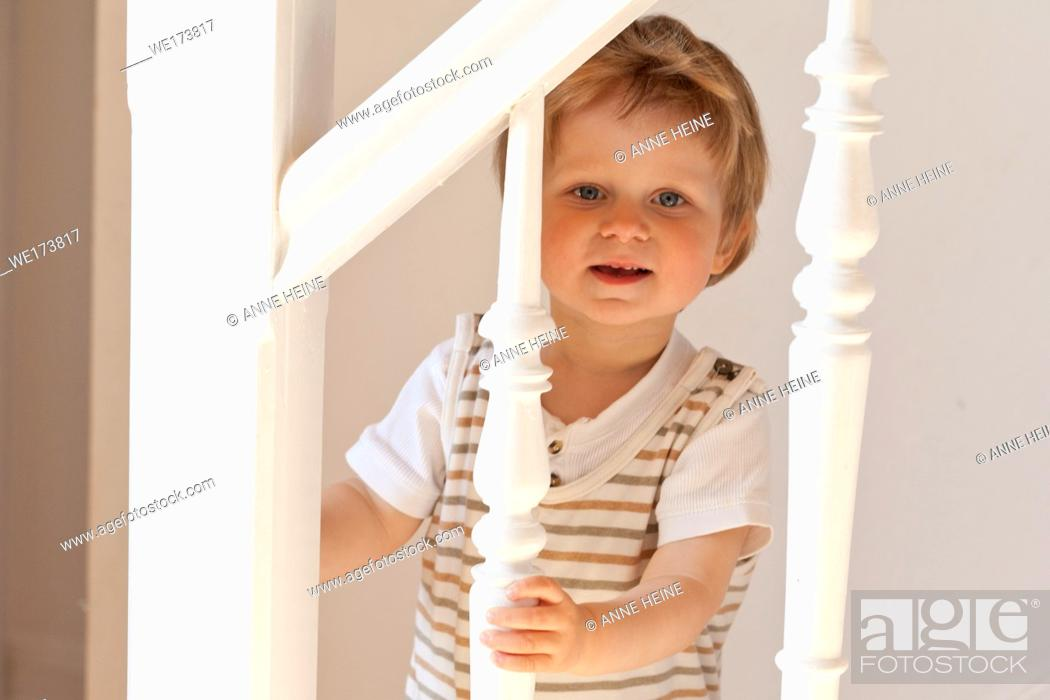 Stock Photo: Boy looking through ballustrade portrait. Germany.