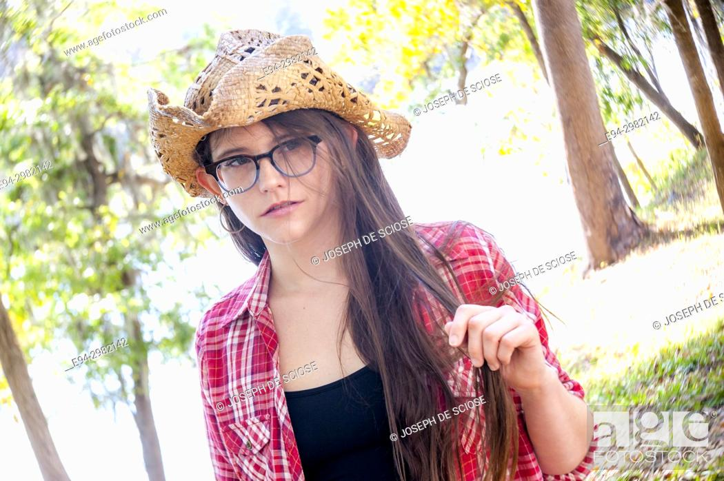 Stock Photo: A casual portrait of a 26 year old woman with long brown hair and big glasses, on a country road.