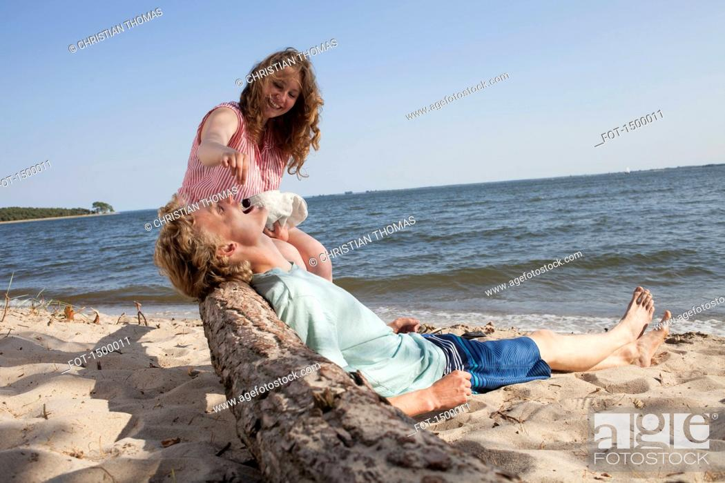 Imagen: Happy friend feeding cherry to man while relaxing at beach.