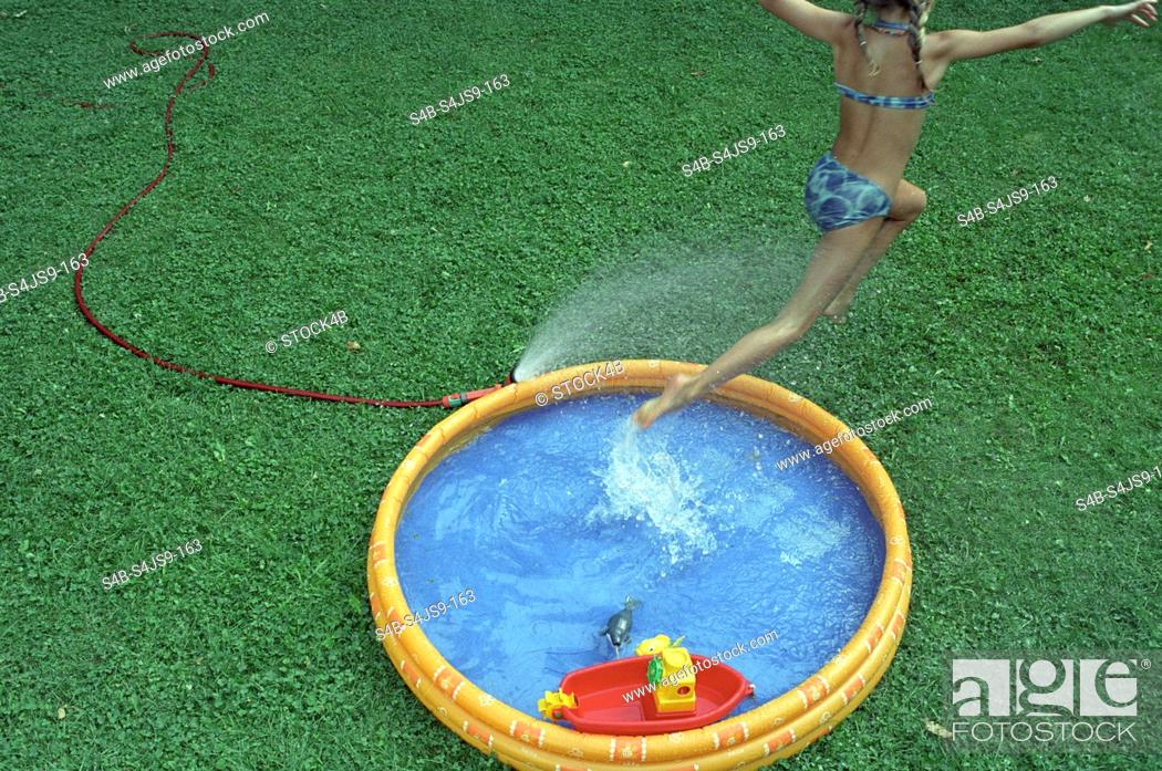 Stock Photo: Girl jumping out of Paddling Pool - Garden - Summer.
