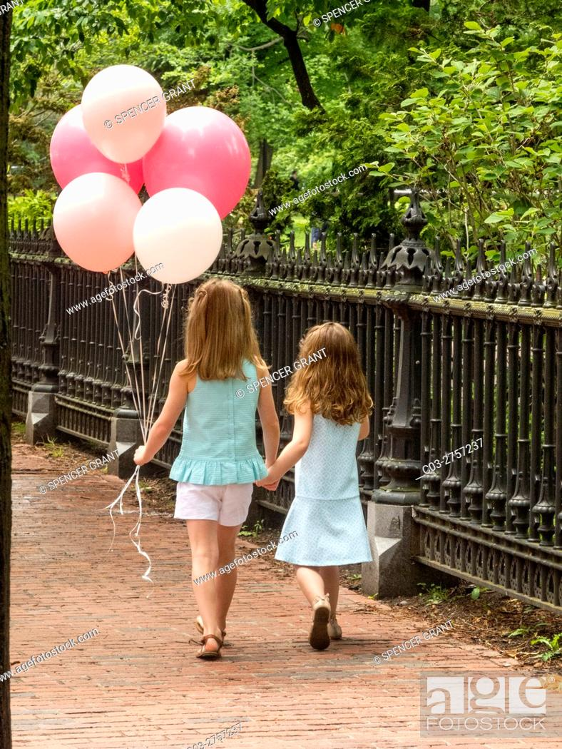 Stock Photo: Two sisters hold hands as they walk past a park in Boston, MA. Note balloons and brick sidewalk.