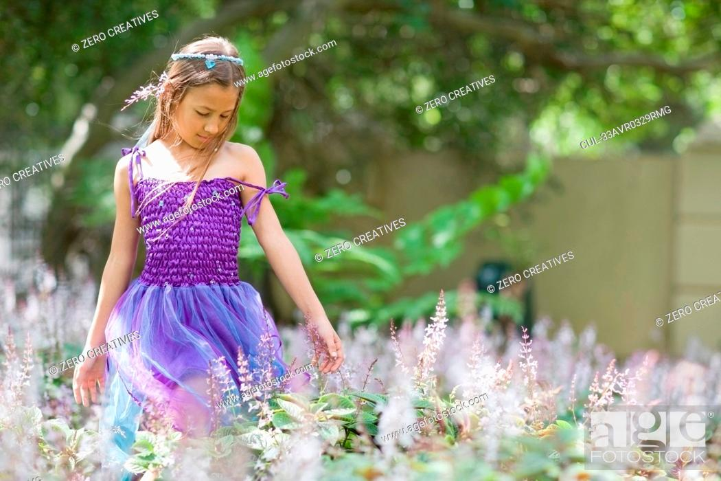 Stock Photo: Girl wearing fairy costume in backyard.