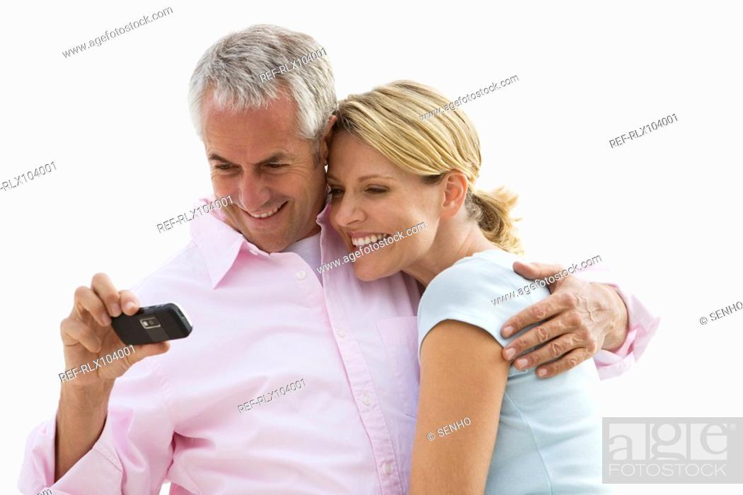 Stock Photo: Mature couple smiling while looking at photos on camera phone.