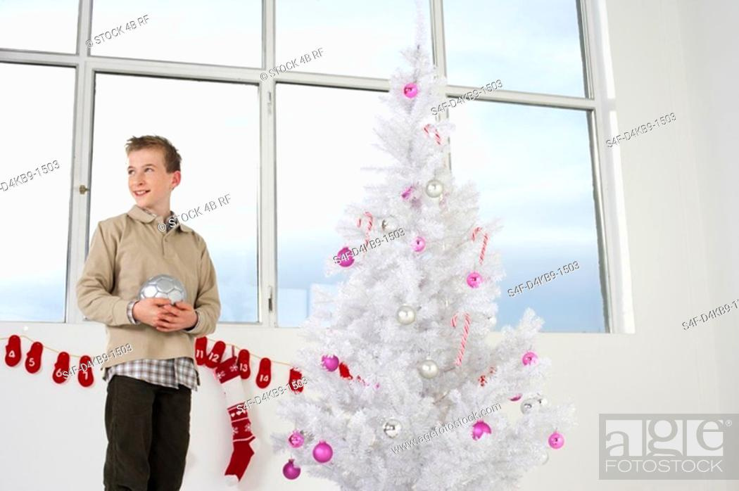 Stock Photo: Boy by a white Christmas tree.