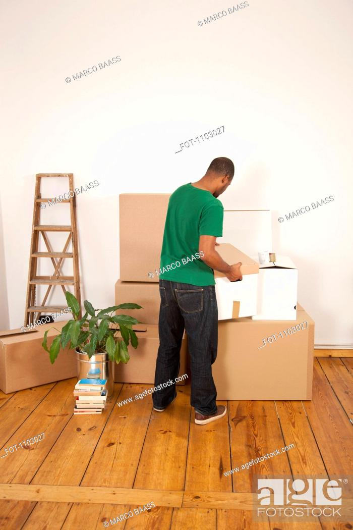 Stock Photo: A man lifting a moving box to put it on top of other boxes.