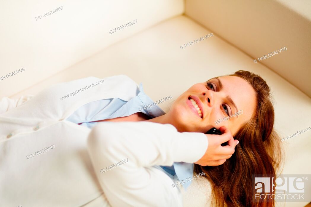 Stock Photo: Close up portrait of a young woman lying on sofa and on the mobile phone.