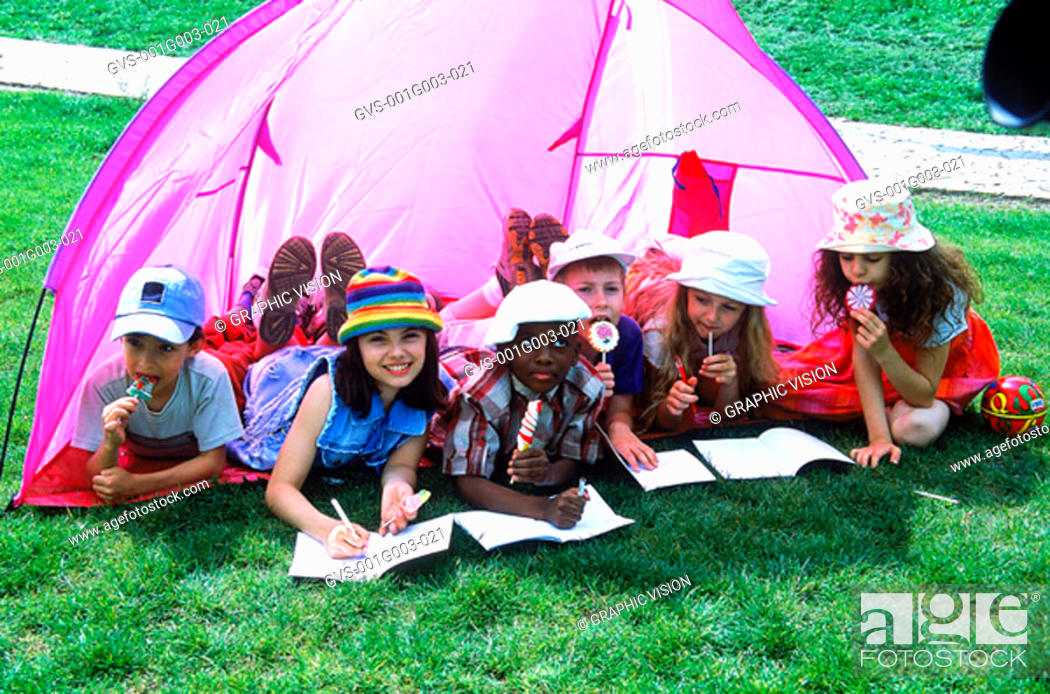 Stock Photo: Young children lying in a tent drawing in books.