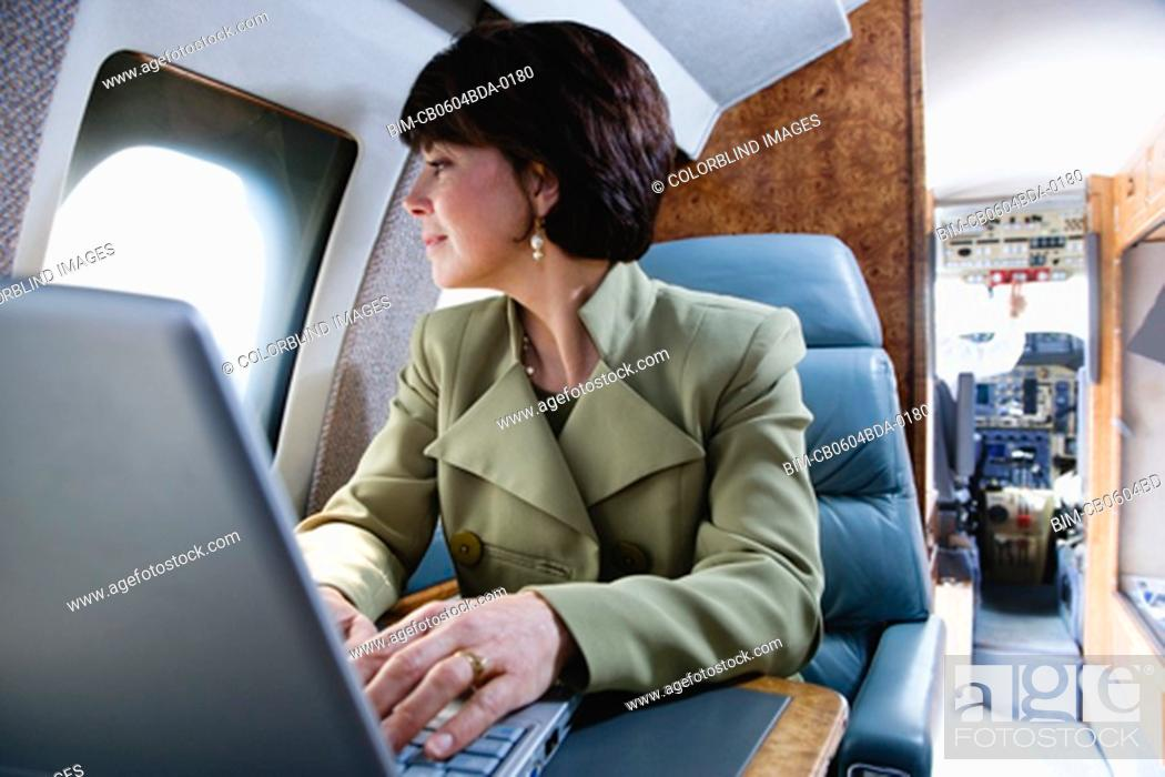 Stock Photo: Businesswoman with laptop on private airplane.