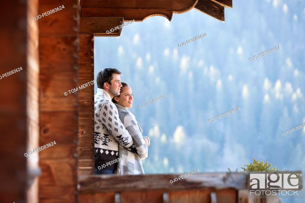 Stock Photo: Couple hugging and looking at view from cabin porch.