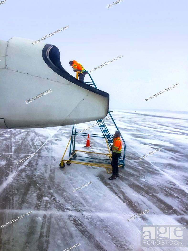 Stock Photo: Two persons service a small aircraft parked on the tarmac in extreme winter conditions, Ontario, Canada.