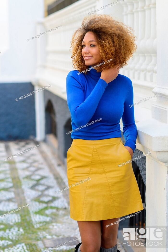 Stock Photo: Funny young African American woman, model of fashion, smiling with afro hairstyle and green eyes wearing blue sweater and yellow skirt in urban background.