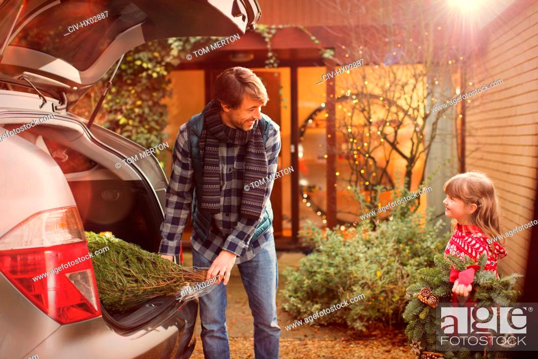 Stock Photo: Father and daughter unloading Christmas tree from car outside house.