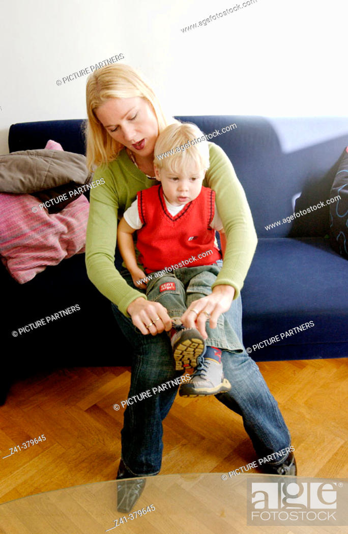 Stock Photo: Mother ties shoe-laces.