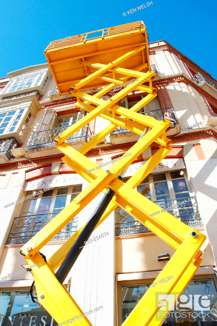 Scissor lift in use to repair or paint building facade, Stock Photo