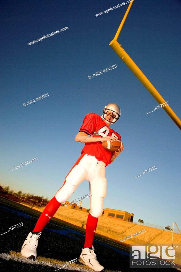 Stock Photo: American football player, in red football strip and protective helmet, standing below goal post, holding ball, portrait surface level, tilt.