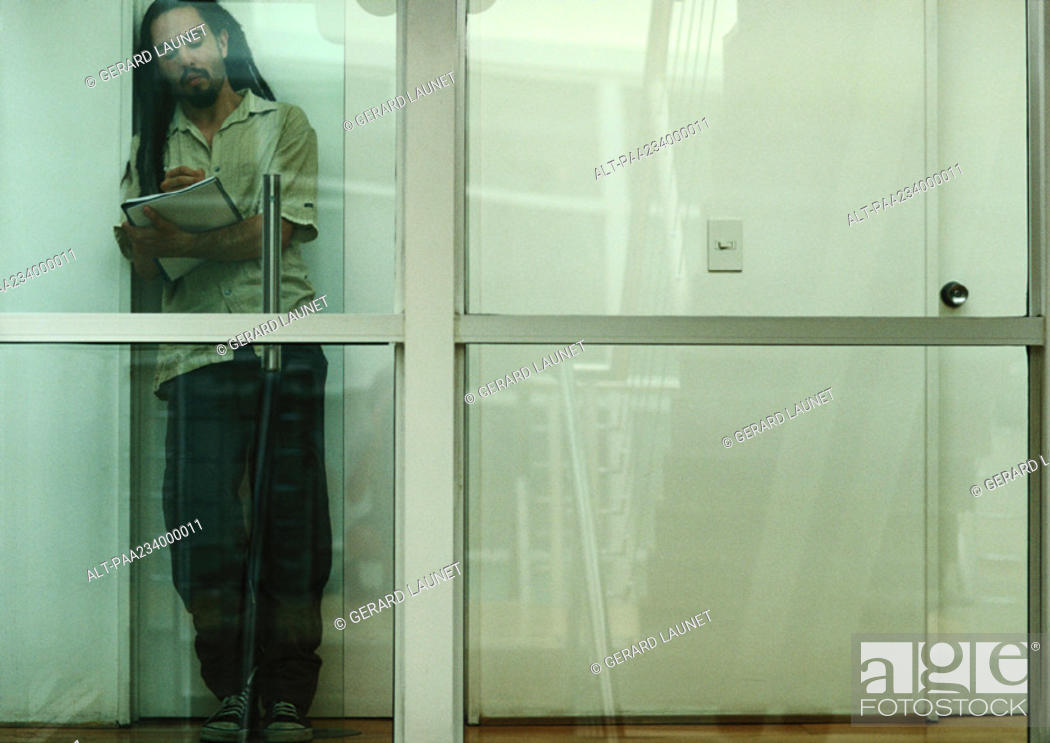 Stock Photo: Man leaning against wall reading, view through glass.