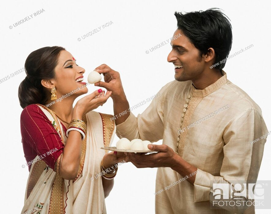 Imagen: Bengali man feeding a rasgulla to his wife.