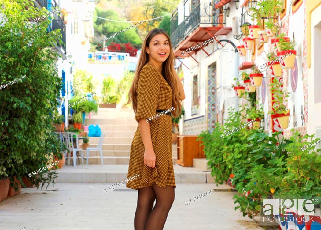 Stock Photo: Young fashion woman walking in Santa Cruz old neighborhood of Alicante, Spain. Beautiful elegant girl visiting southern Europe.