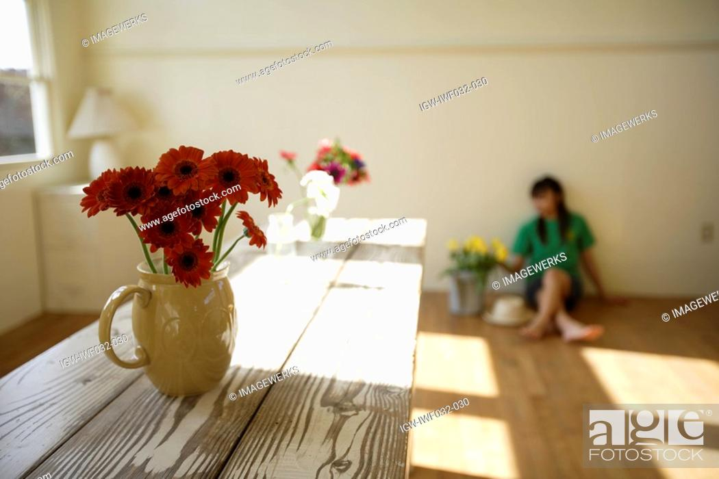 Stock Photo: Woman with flowerpot in foreground.