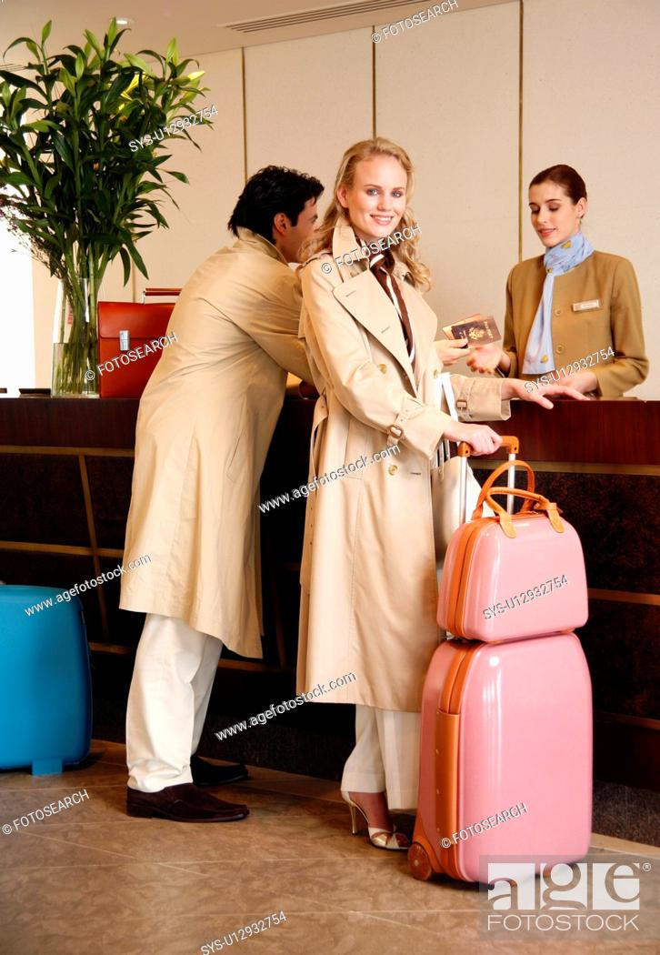Stock Photo: Couple checking in at hotel reception.