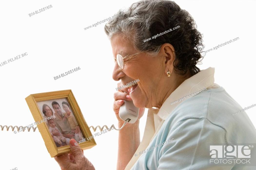 Stock Photo: Senior Hispanic woman talking on telephone.