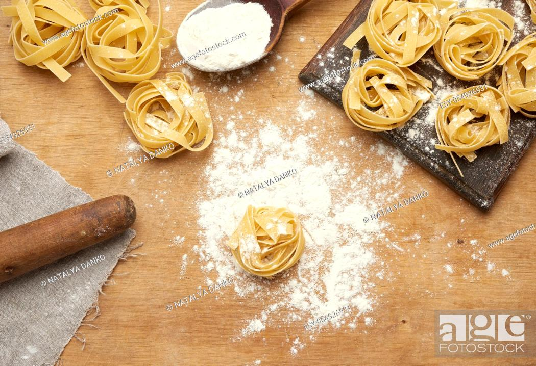 Stock Photo: raw fettuccine pasta on a brown wooden board and a wooden vintage rolling pin, top view.