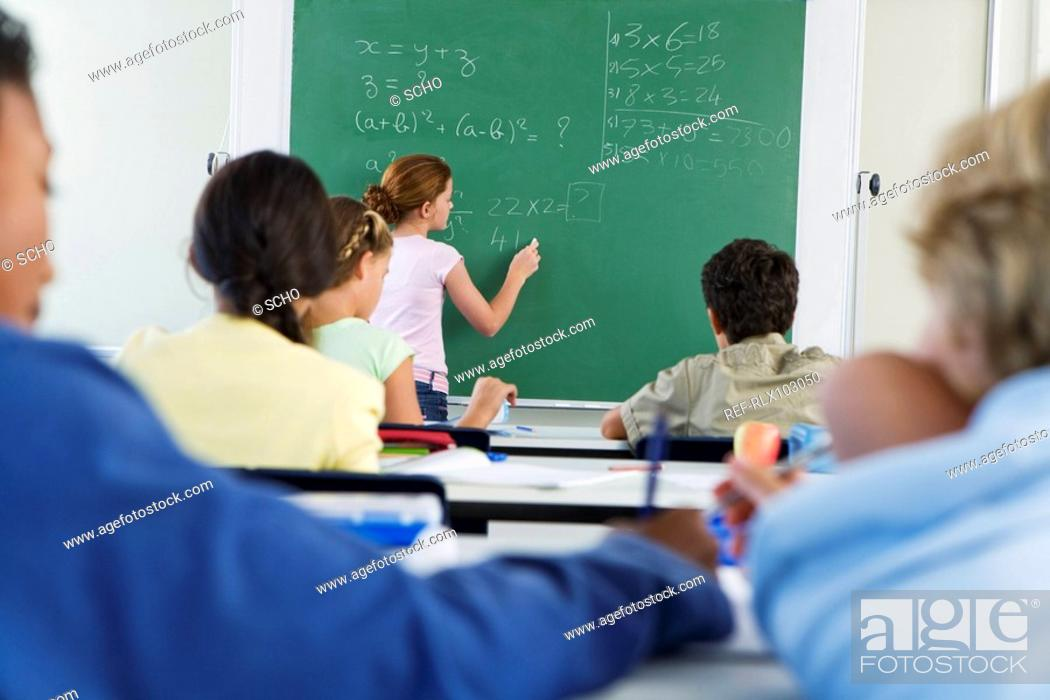 Stock Photo: Group of school children 10-13 in classroom looking at blackboard.