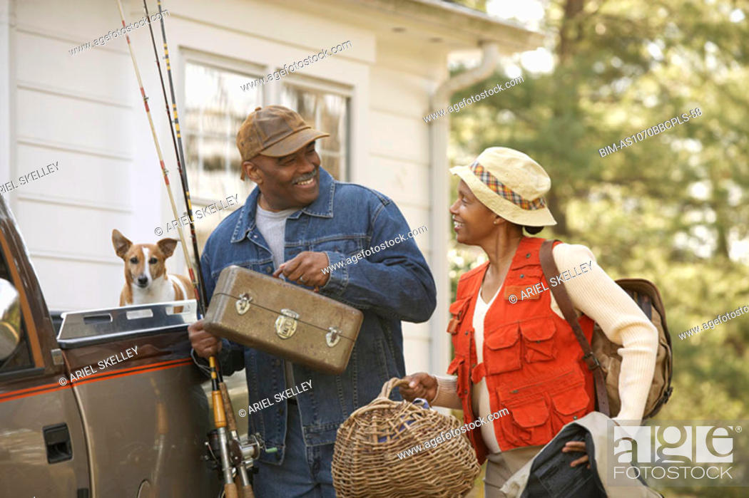 Stock Photo: Middle-aged African American couple carrying fishing equipment.
