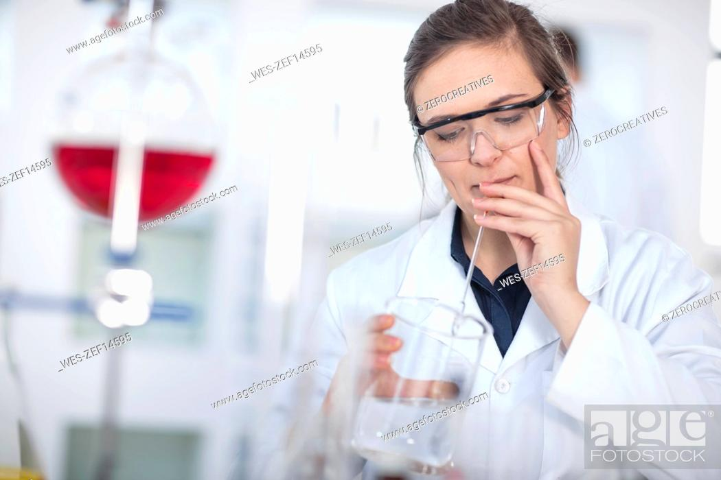 Imagen: Scientist working in lab using beaker and pipet.