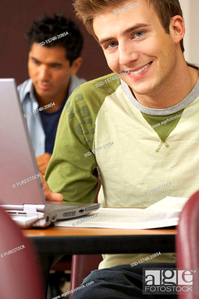 Stock Photo: Two college students sitting in a lecture hall and using laptops.