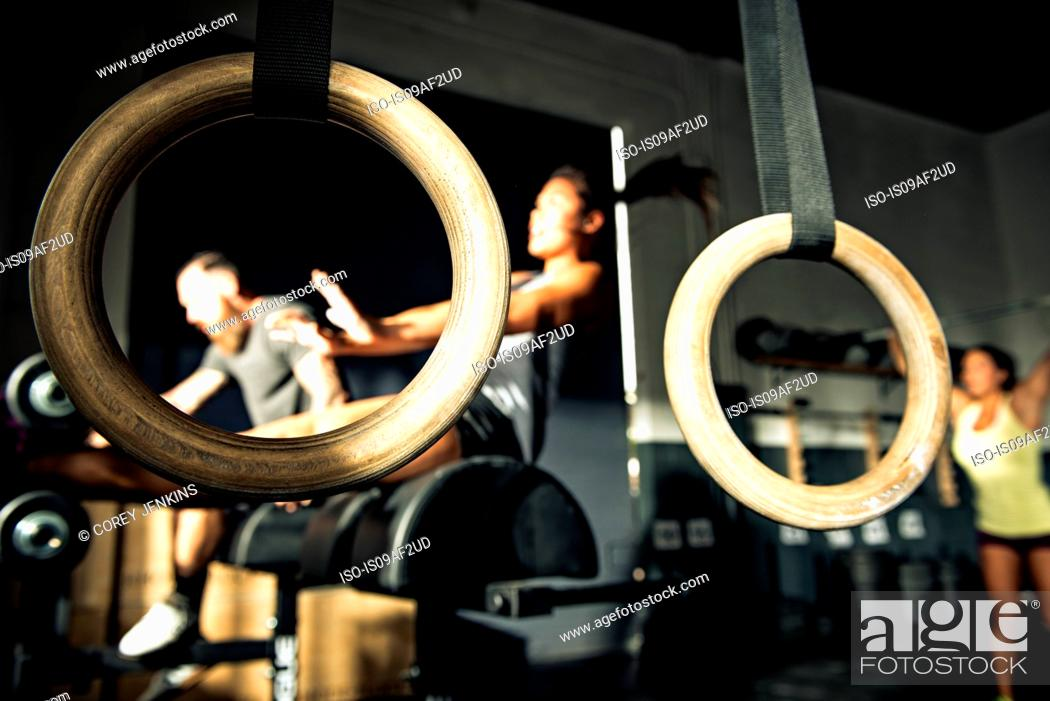 Stock Photo: Close up of gymnasium rings with people training in background.