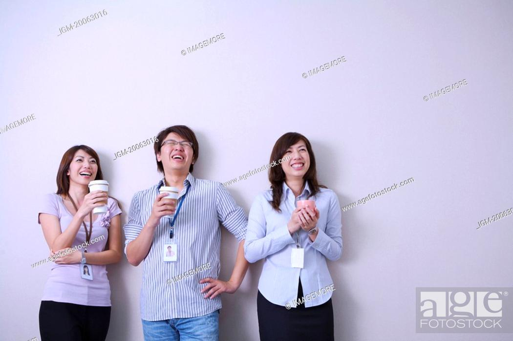 Stock Photo: Three colleagues holding coffee and smiling happily together.