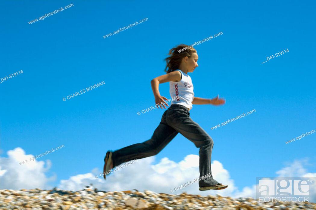 Stock Photo: Girl running along seaside kicking.