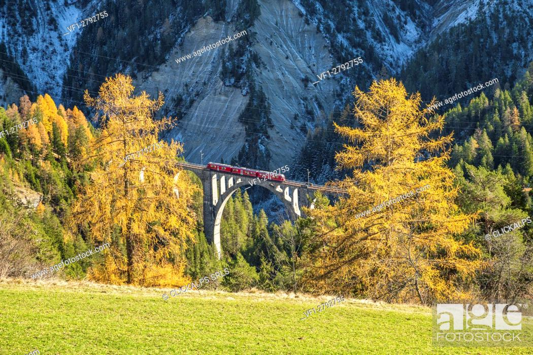Stock Photo: Bernina Express passes through Wiesner Viadukt surrounded by colorful woods Canton of Graubünden Switzerland Europe.