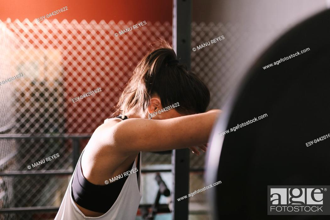 Stock Photo: Athletic young woman concentrates before to do some weightlifting exercises.