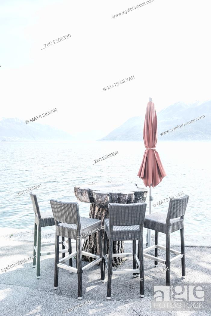 Stock Photo: Chairs and a table with parasol on the waterfront on alpine lake Maggiore in Ticino, Switzerland.
